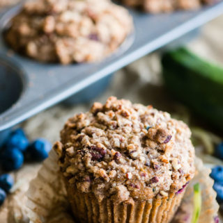 Zucchini Blueberry Muffins with Stresel Topping in wrapper with fresh blueberries